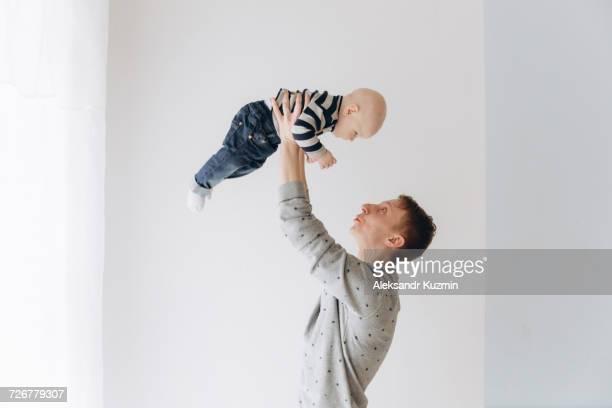 caucasian father lifting baby son - levantar imagens e fotografias de stock