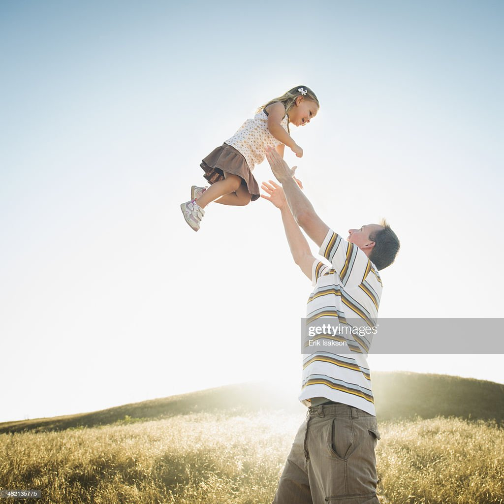 Caucasian father lifting daughter overhead in rural field : Stock Photo