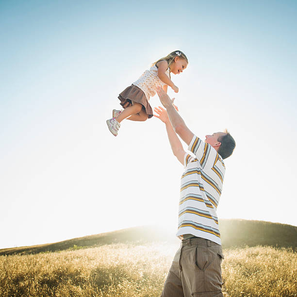 Caucasian Father Lifting Daughter Overhead In Rural Field Wall Art
