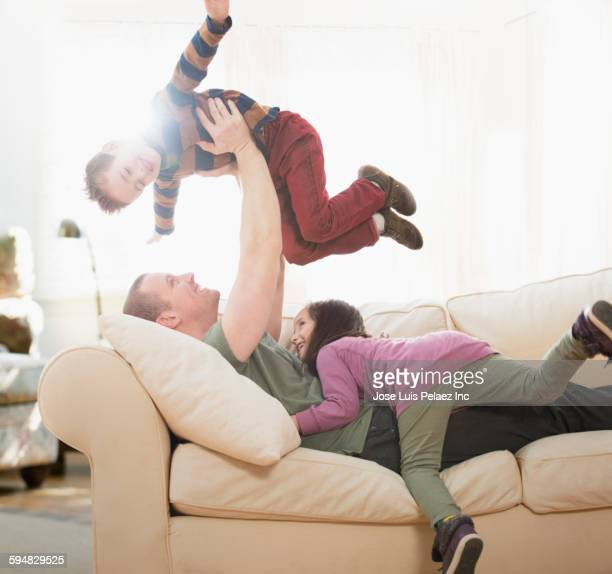 Caucasian father playing with children on sofa
