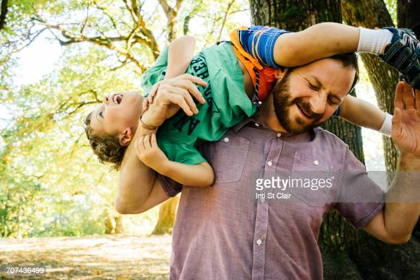 Caucasian father playing with son on shoulder