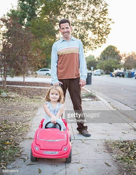 Caucasian father pushing daughter in toy car