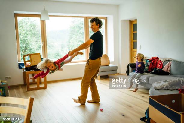 Caucasian father spinning daughter by arm and leg in livingroom