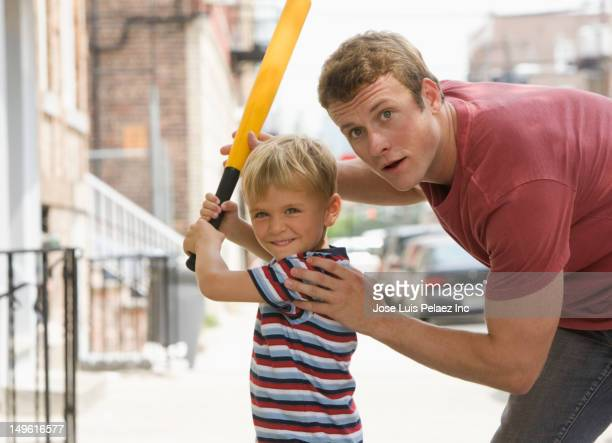Caucasian father teaching son to play baseball