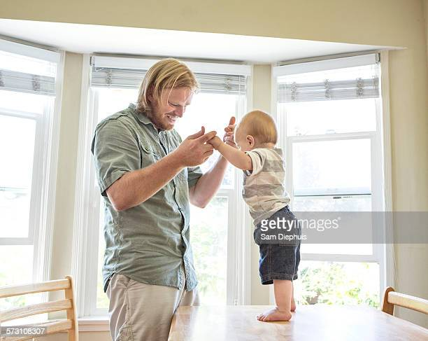 Caucasian father teaching son to stand on table