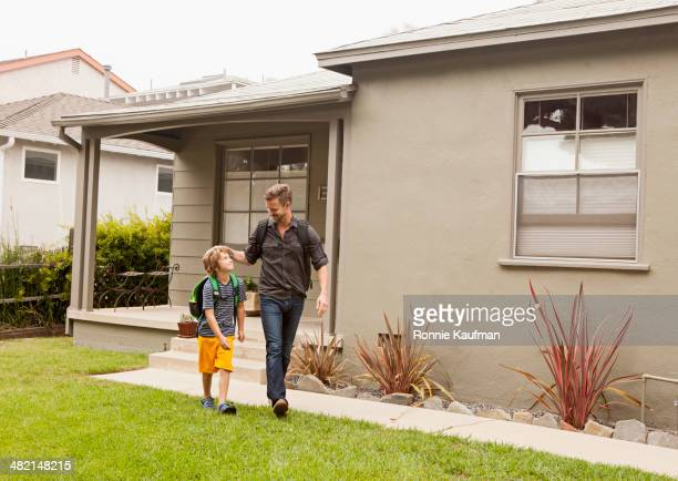 caucasian father walking son to school - gemeinsam gehen stock-fotos und bilder