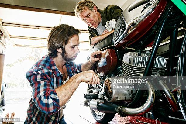Caucasian father watching son repairing motorcycle in garage