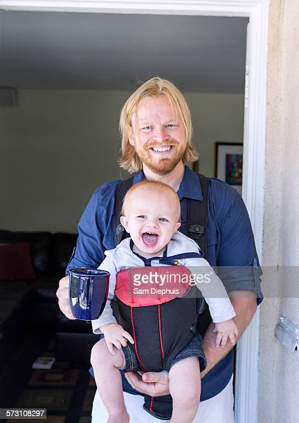 Caucasian father wearing son in harness in doorway