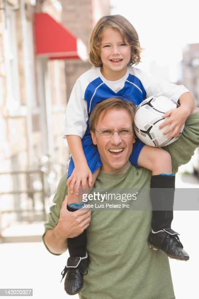 Caucasian father with son in soccer uniform