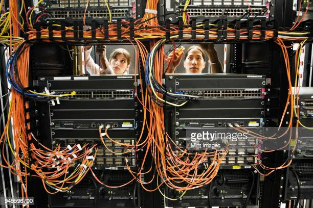 Caucasian female and Asian American male technicians working on a CAT 5 cable bundling system in a large computer server room.