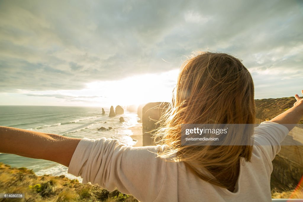 Caucasian female arms outstretched at sunset : Stock Photo