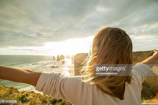 Caucasian female arms outstretched at sunset