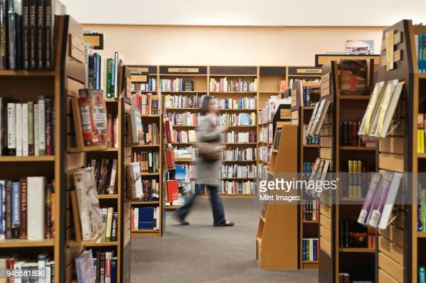 caucasian female browsing through books in a bookstore. - book store stock photos and pictures