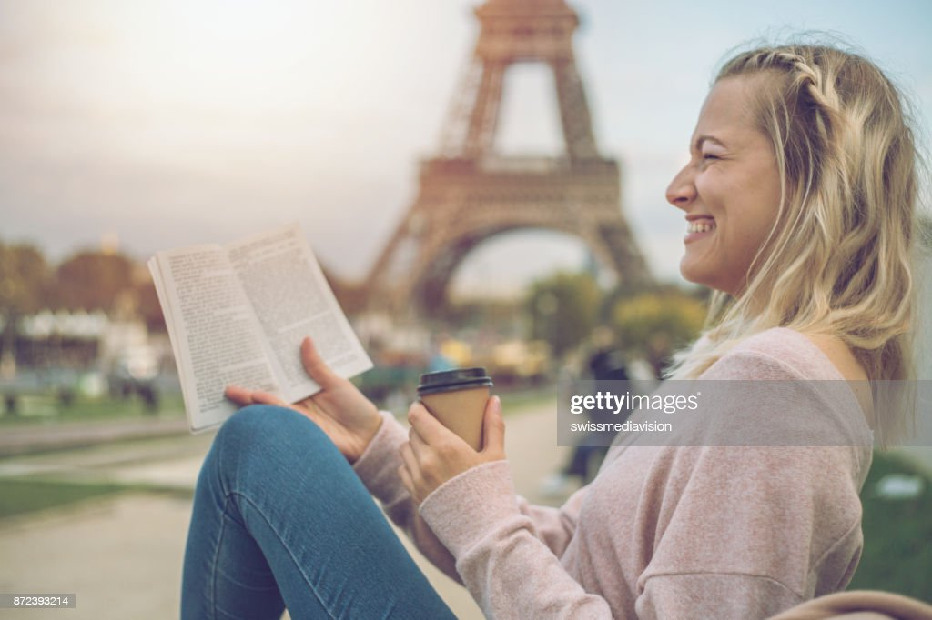 Caucasian blond girl sitting on a bench in front of the Eiffel Tower in Paris, France and reading a book