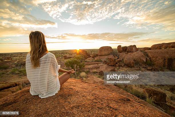 Caucasian female exercising yoga at sunrise