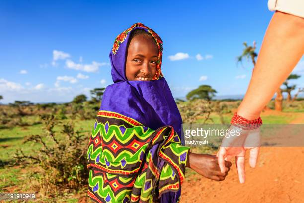 caucasian female is holding young african child's hand - altruism stock pictures, royalty-free photos & images