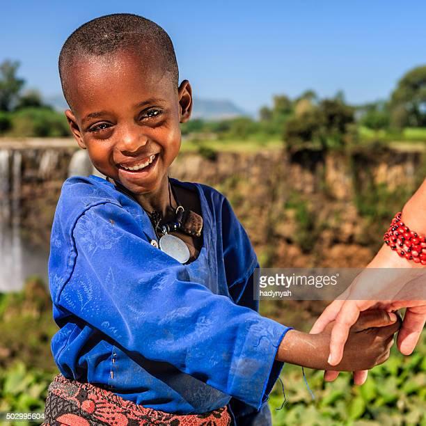 Kaukasisch weibliches hält junge afrikanische Kind hand