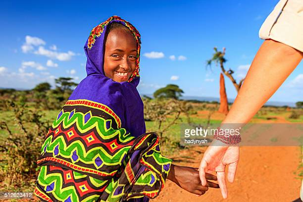 caucasian female is holding young african child's hand - social inequality stock pictures, royalty-free photos & images