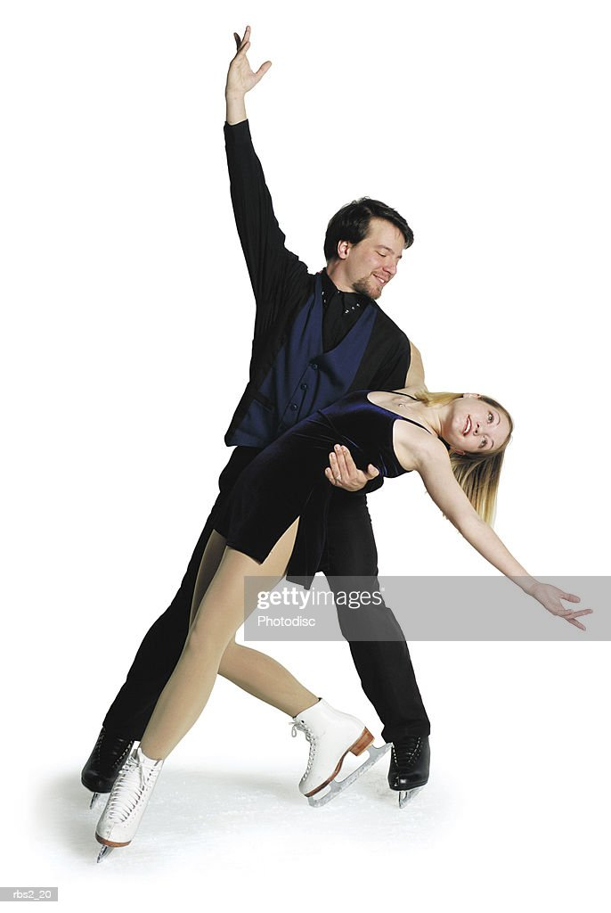 caucasian female leans back on the arm of caucasian male ice skating partner with outstretched arms : Foto de stock
