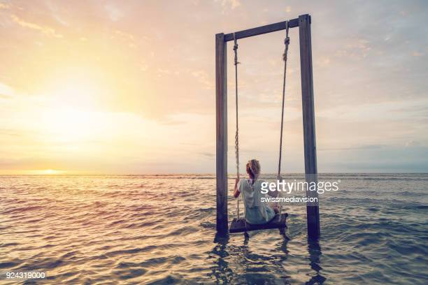 caucasian female playing on swing by the sea at sunset, indonesia - gili trawangan stock photos and pictures