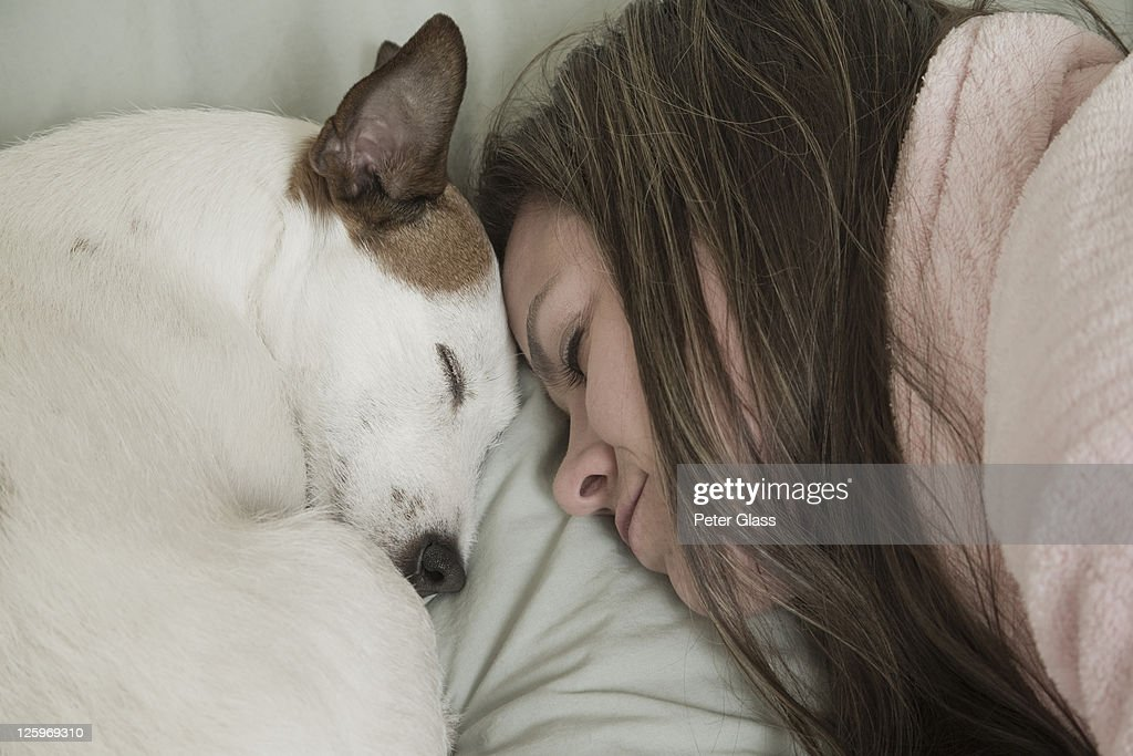 Caucasian female (31 years old) sleeping with her pet dog : Stock Photo
