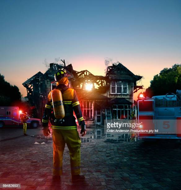 Caucasian firefighter at burned house