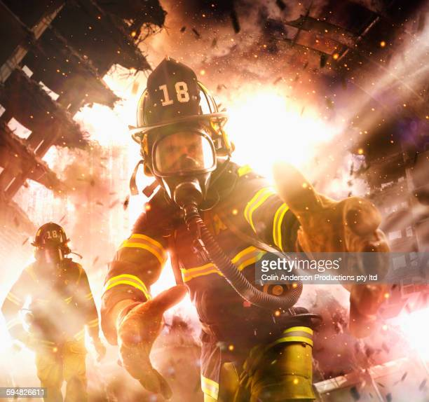 Caucasian firefighter reaching into burning building