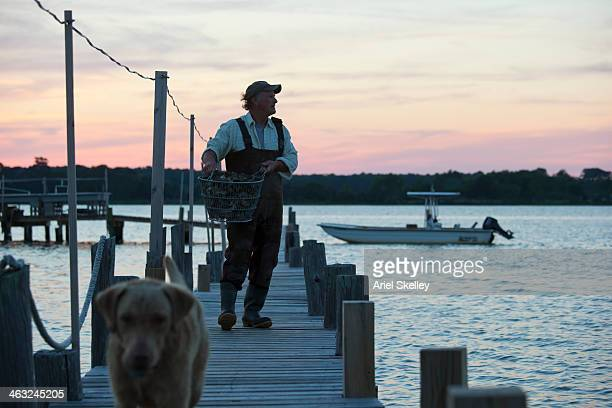 Caucasian fisherman carrying catch on wooden pier