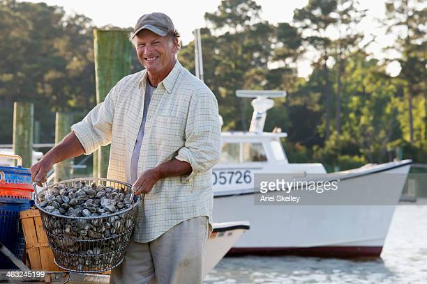caucasian fisherman harvesting oysters from boat - chesapeake bay stock pictures, royalty-free photos & images