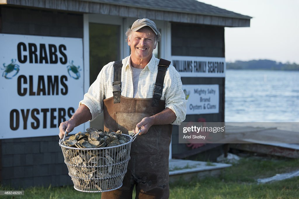 Caucasian fisherman holding basket of oysters : Stock Photo