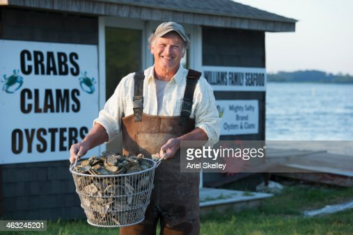 Caucasian fisherman holding basket of oysters