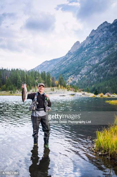 Caucasian fisherman holding catch in river