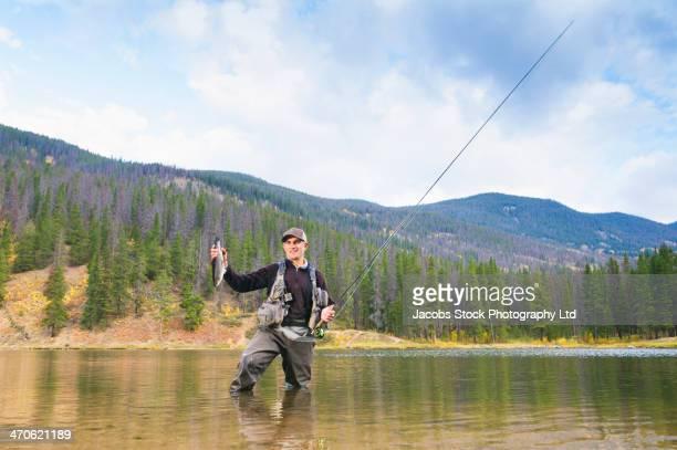 Caucasian fisherman holding catch in river