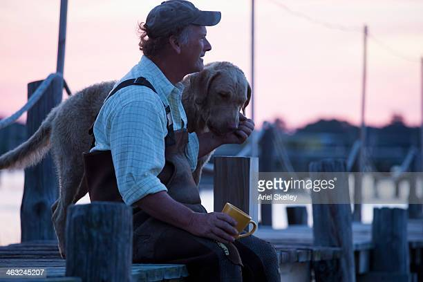 Caucasian fisherman relaxing with dog on wooden pier