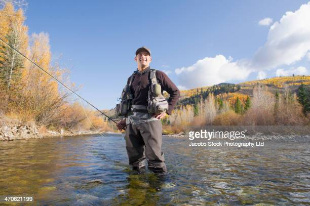 Caucasian fisherman smiling in river