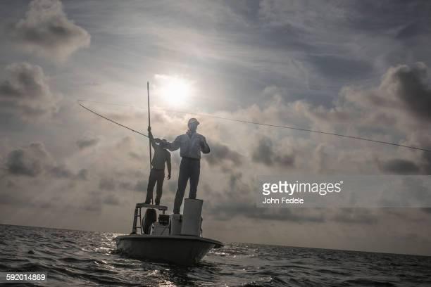 Caucasian fishermen casting lines on boat