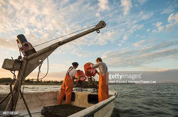 Caucasian fishermen throwing bait into water