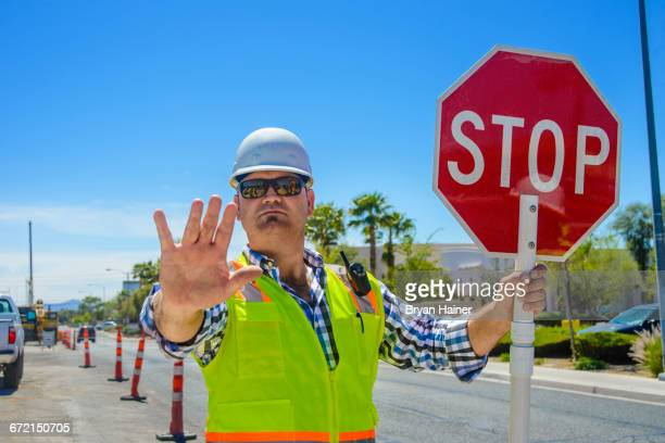 caucasian flagger gesturing stop with stop sign - stop sign stock pictures, royalty-free photos & images