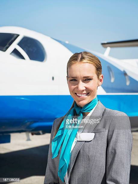 Caucasian flight attendant smiling on runway