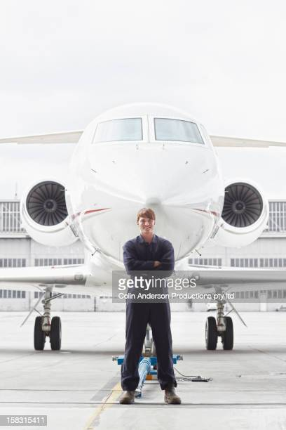 Caucasian flight engineer standing near jet