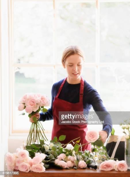 Caucasian florist arranging roses