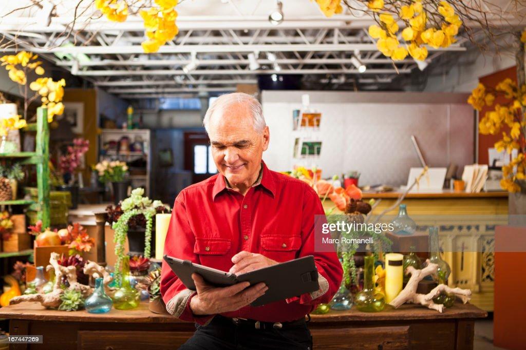 Caucasian florist using tablet computer in shop : Stock Photo