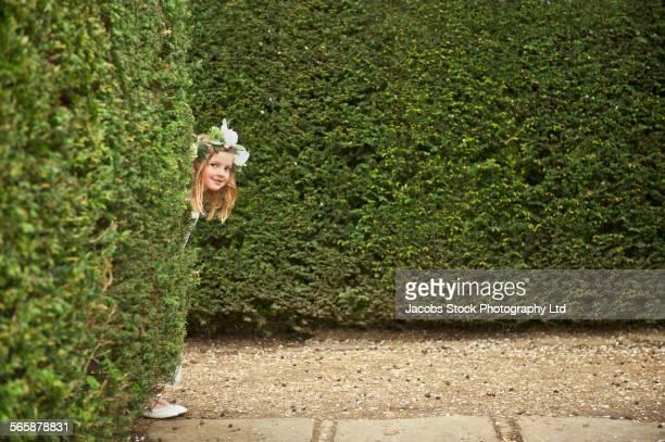Caucasian flower girl peeking around hedges in garden