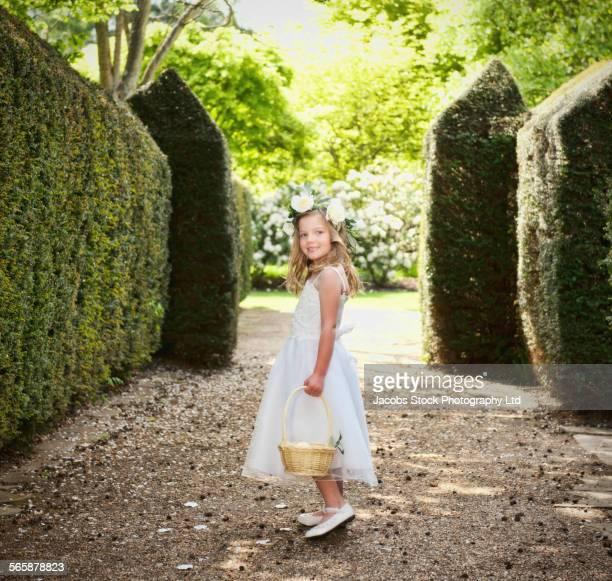 Caucasian flower girl sprinkling petals in garden