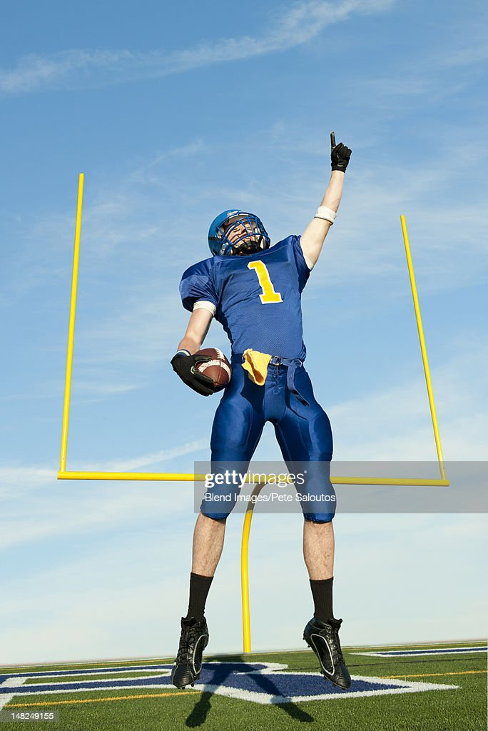 Caucasian football player cheering for victory : Stock Photo