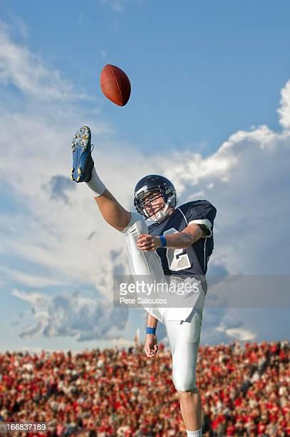Caucasian football player kicking ball