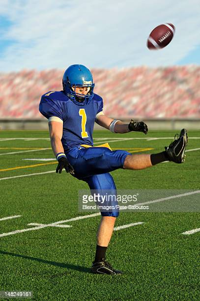 caucasian football player kicking football - punt kick stock pictures, royalty-free photos & images