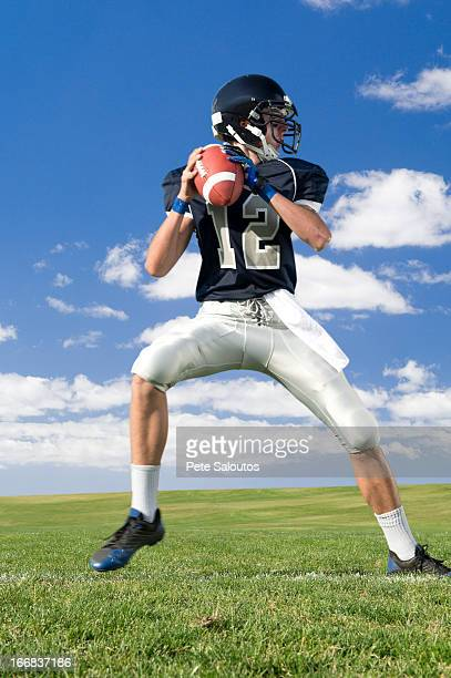 caucasian football player poised on field - quarterback stock-fotos und bilder