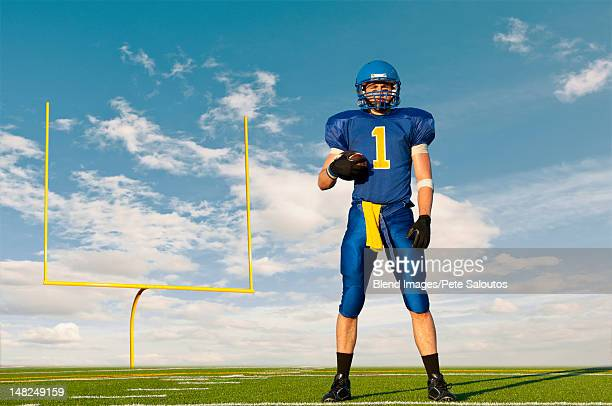 caucasian football player standing with football - safety american football player stock pictures, royalty-free photos & images