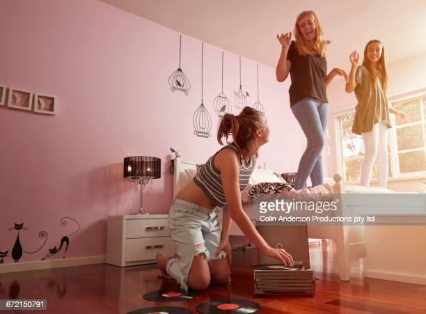 Caucasian friends dancing on bed to record player